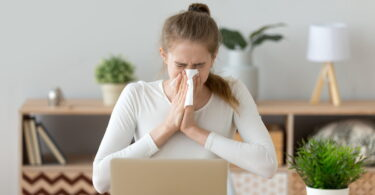 Young sick woman sitting at workplace, blowing nose, holding handkerchief