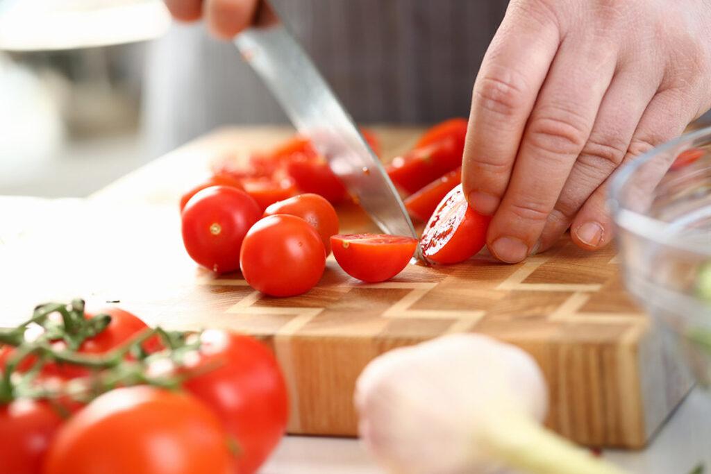 Knife slicing cherry tomato