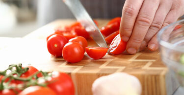 Knife slicing cherry tomato