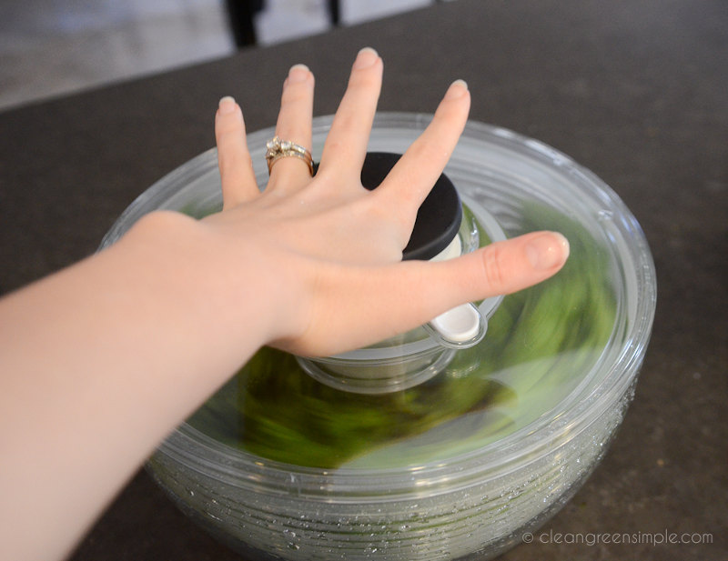 Woman's hand pressing down on salad spinner