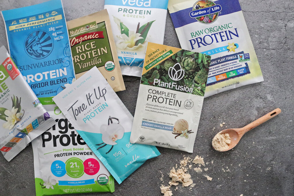 Several vegan protein powders with a wooden spoon