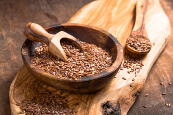 Flax Seeds In Bowl On Wooden Board