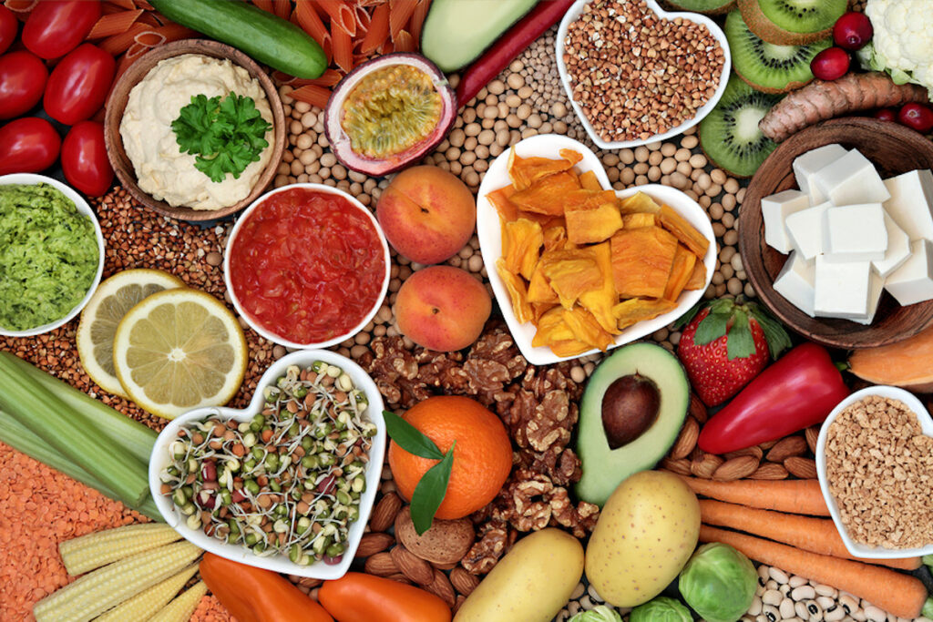 Healthy plant based diet foods with grains, nuts, dips, bean curd, fruit, vegetables, legumes and spices.