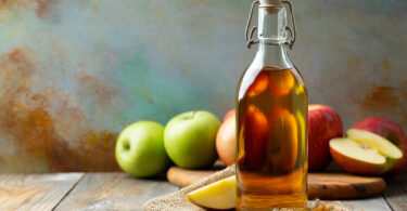 Bottle of apple organic vinegar or cider on wooden background