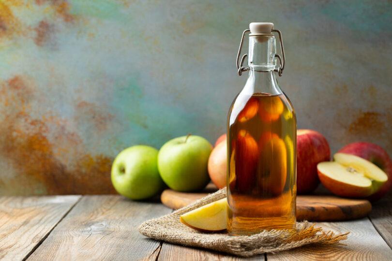 Bottle of apple organic vinegar or cider on wooden background