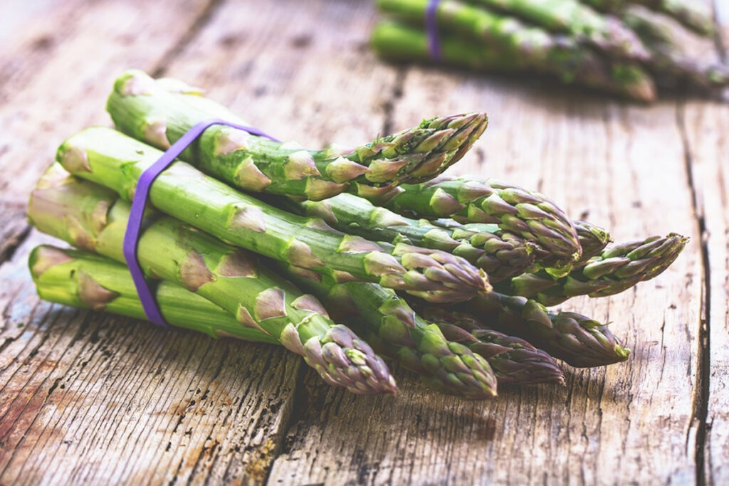 Fresh, raw asparagus on a rustic wooden table