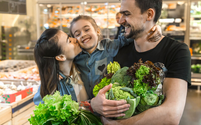Happy husband and wife with a kid buys vegetables