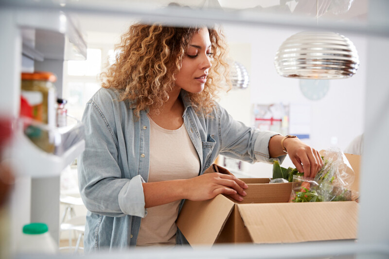 Woman opening meal kit delivery box