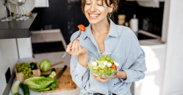 Young, thin, and cheerful woman eating healthy salad in the kitchen at home.