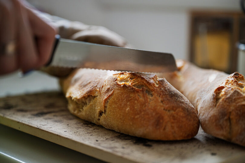 Knife cutting into freshly baked home made sourdough loaf of bread.