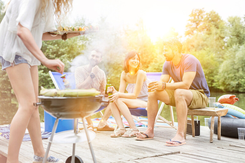 Woman preparing food on barbecue grill with friends on pier