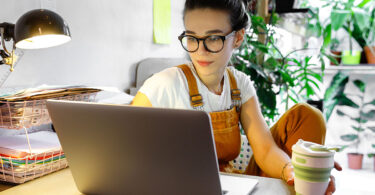 Young female in glasses sitting at computer with house plants in background