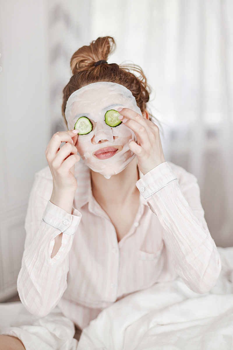 Young woman with face mask treatment putting cucumbers on eyes.