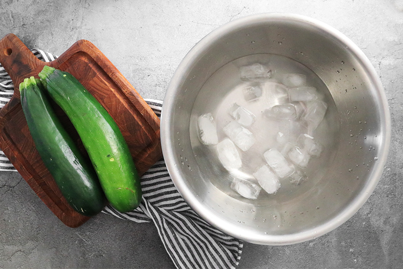 Zucchini on cutting board next to ice bath