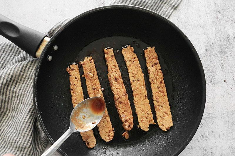 frying tempeh bacon in a pan