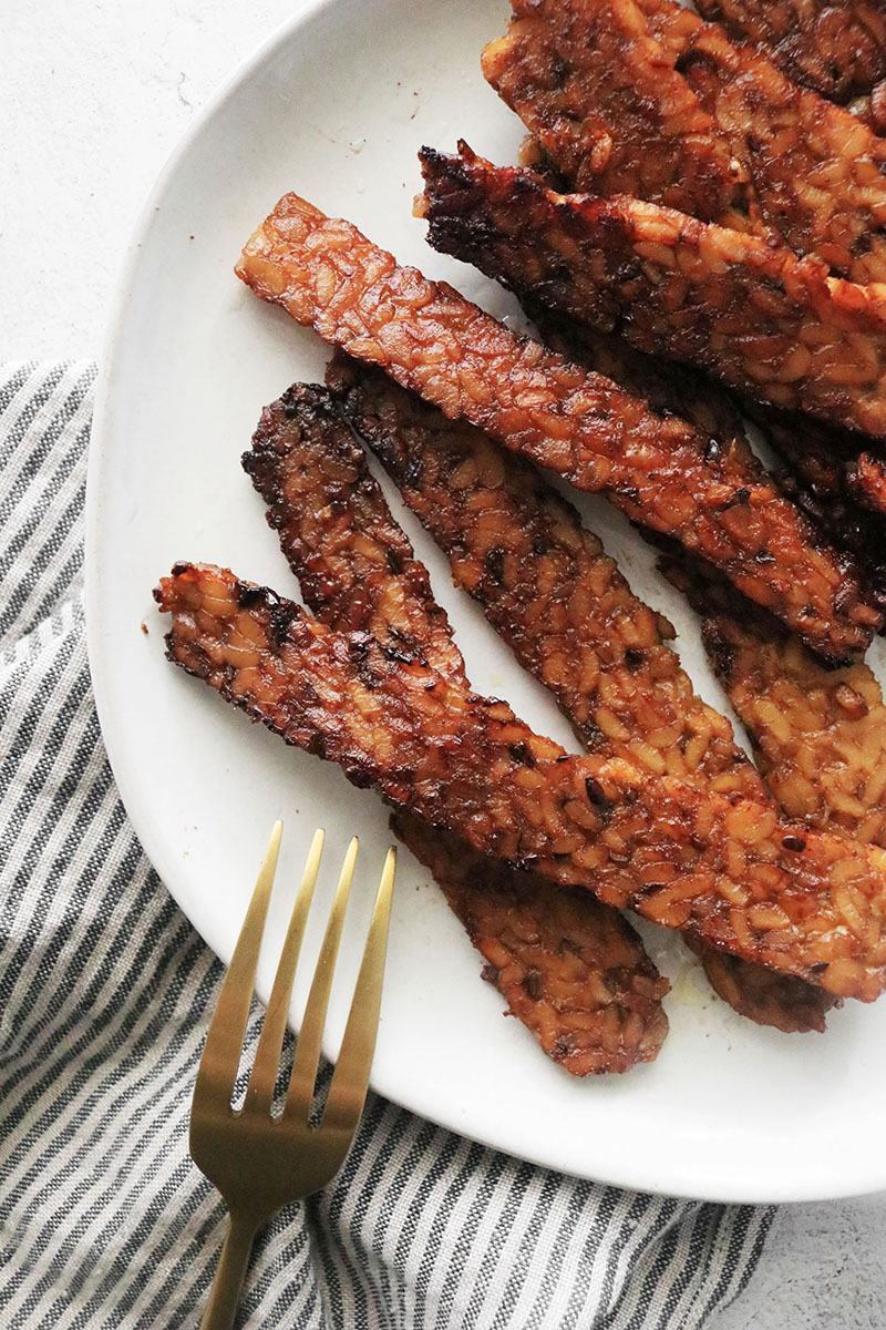tempeh bacon on a white plate with a fork