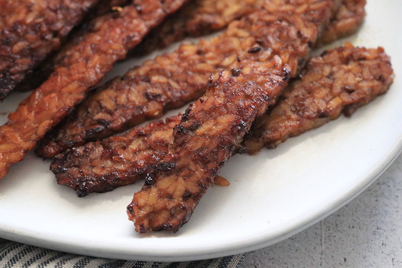 smokey, delicious tempeh bacon on a white plate