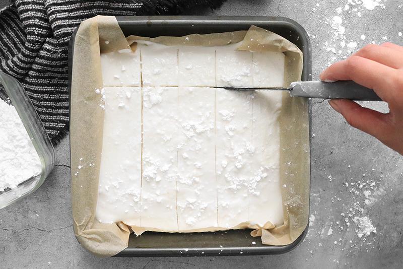 slicing vegan marshmallows in a pan