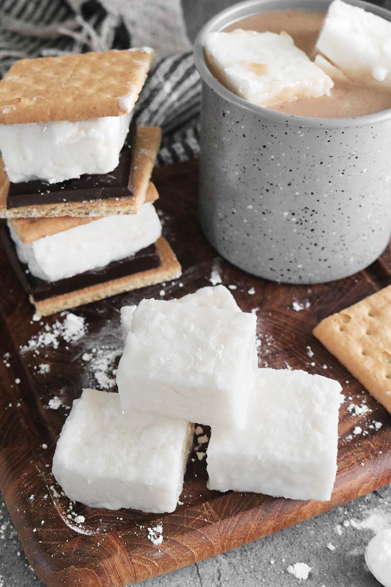 vegan marshmallows on a cutting board with coffee and s'mores