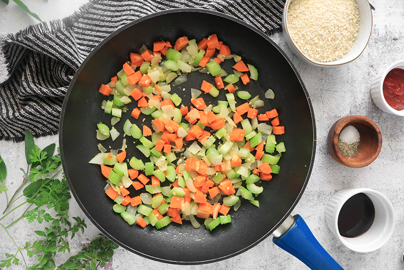 carrots, celery, and onions cooking in a pan