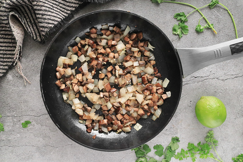 cooking mushrooms and onions in a skillet