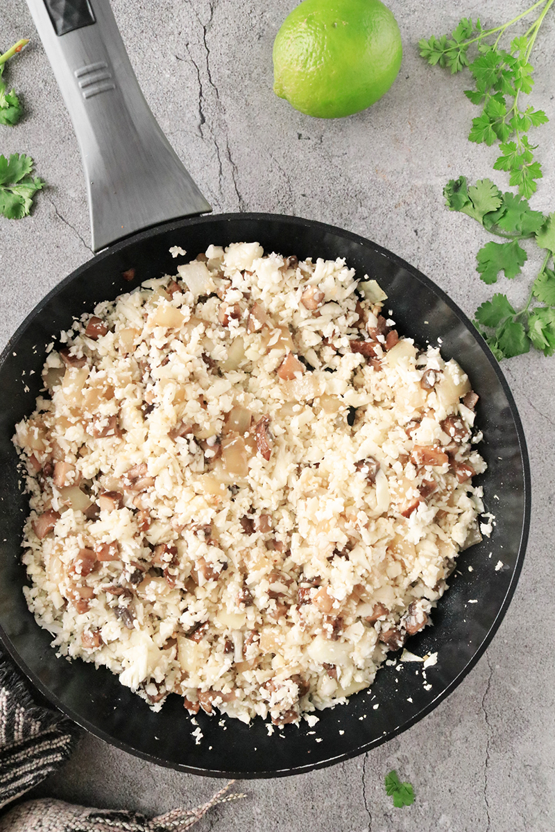 cooking mushrooms, onions, and cauliflower rice in a skillet