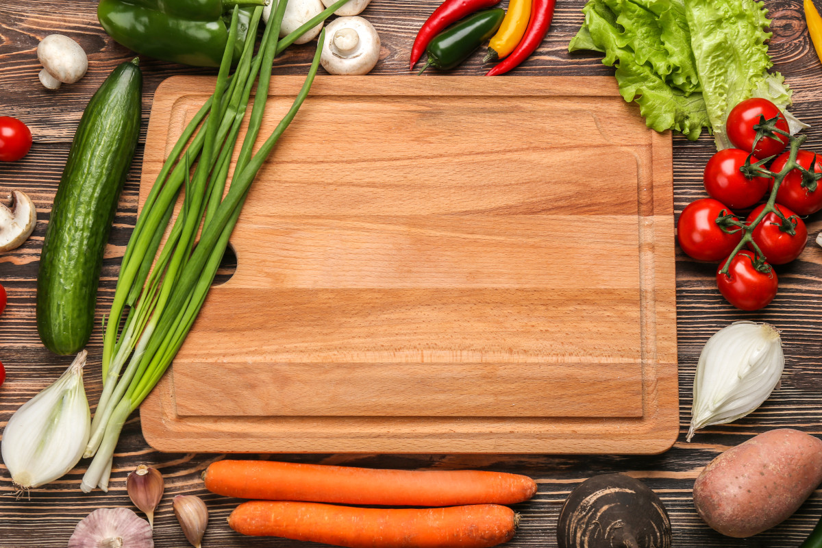 Wooden cutting board surrounded by vegetables