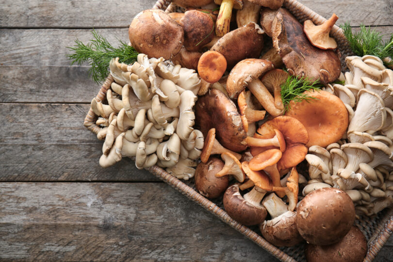 Wicker tray with different types of raw mushrooms on wooden table