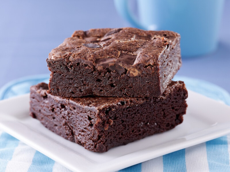 Two brownies stacked on a while plate with a blue background
