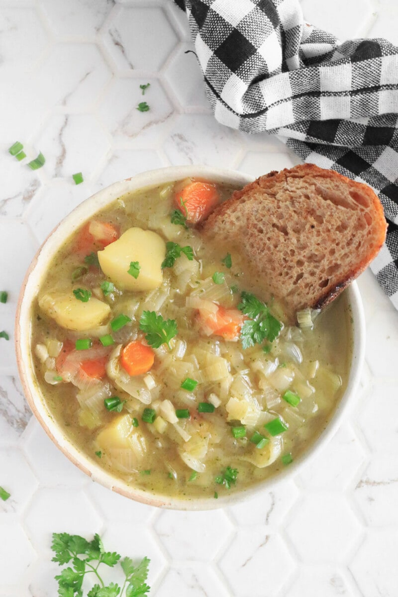 Chunky Vegan Potato Leek Soup in a bowl served with bread on a white background