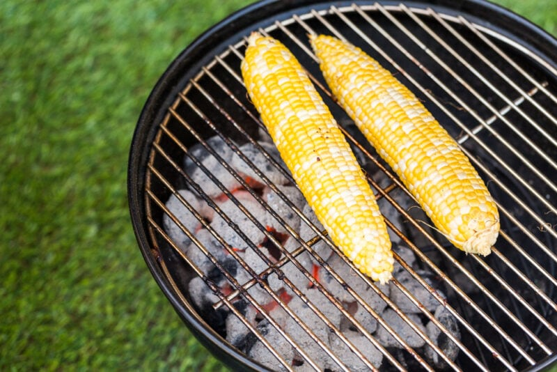 Two ears of corn reheating on a charcoal grill