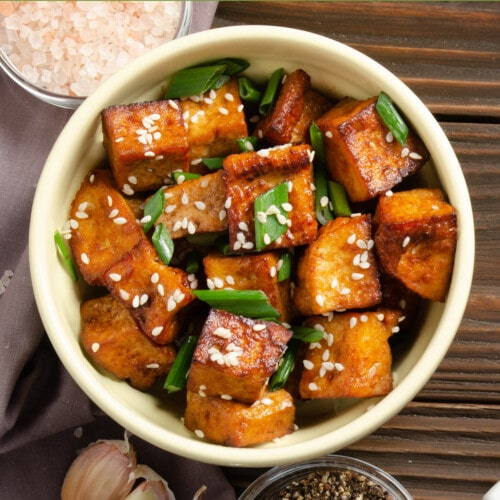 crispy stir fried tofu with chives on a wooden table