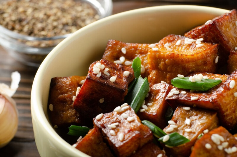 Close Up view at crispy fried tofu pieces with chives and sesame in clay dish