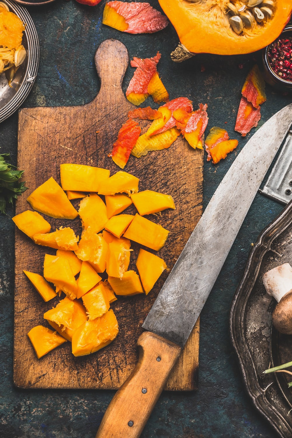 Rustic cutting board with chopped pumpkin and an old knife