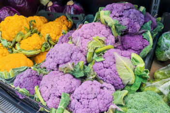 Bunches of fresh yellow, purple and green cauliflower heads at the farmers market