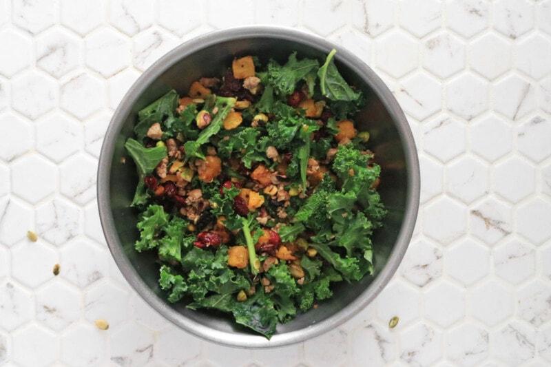 fall harvest salad ingredients tossed in a metal bowl