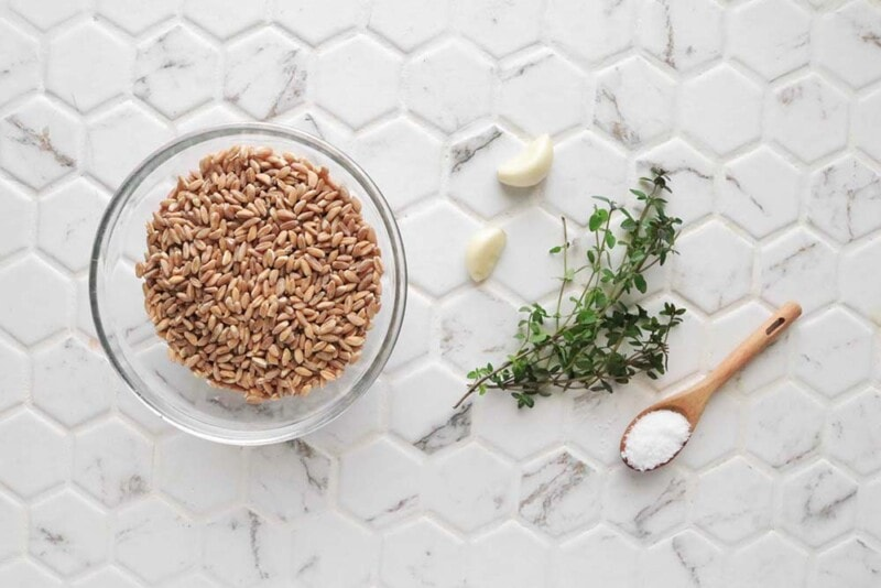 Uncooked farro in a glass bowl with fresh garlic cloves, herbs, and salt