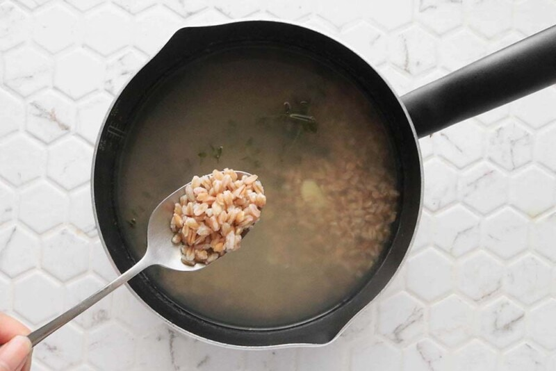 A spoon of uncooked farro above a pot of water