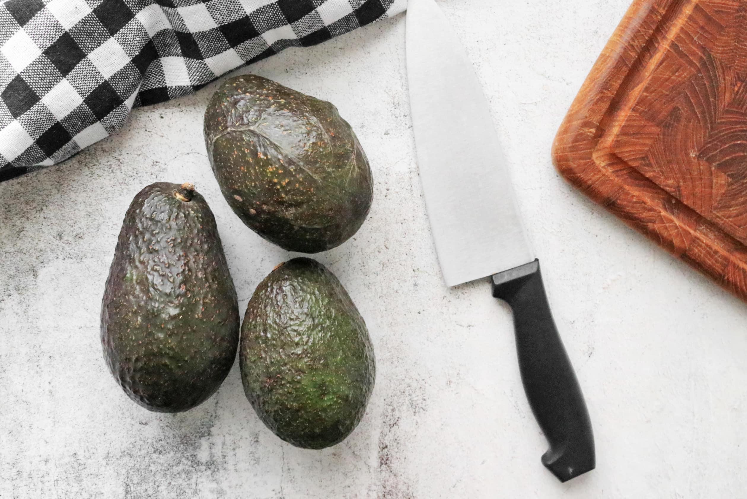 3 Avocados next to a chef's knife