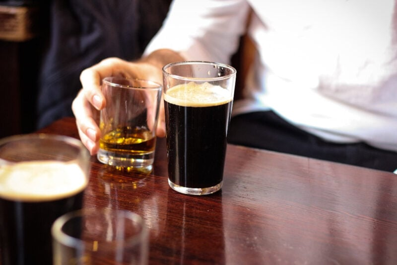 Man sitting at table with stout beer and whiskey