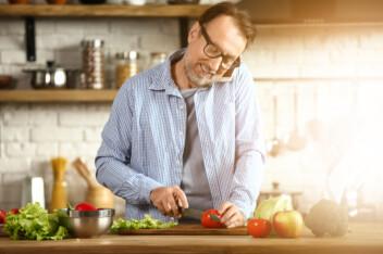 Man Cutting Veggies and talking on phone
