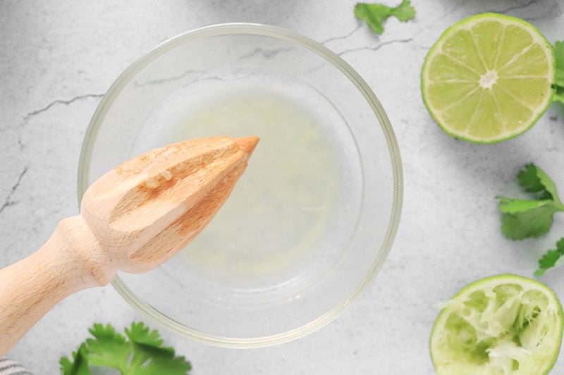 Citrus reamer with lime juice in a glass bowl