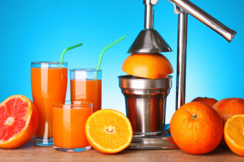 Manual lever Juicer with oranges and grapefruit on blue background