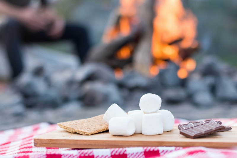 marshmallows and s'mores ingredients near a campfire