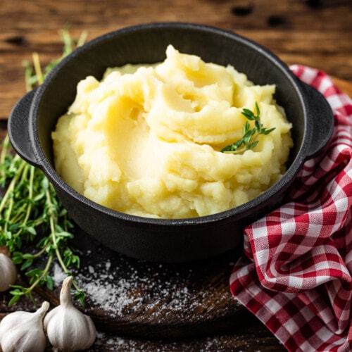 Mashed potatoes in a cast iron crock on a wooden table