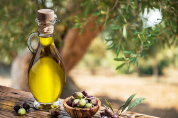 Bottle of olive oil and olive berries are on the wooden table