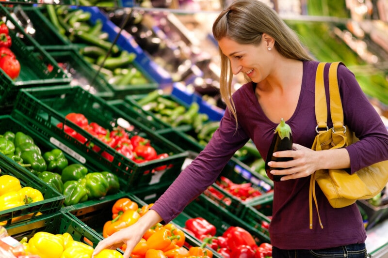 young woman shopping for produce in a grocery store
