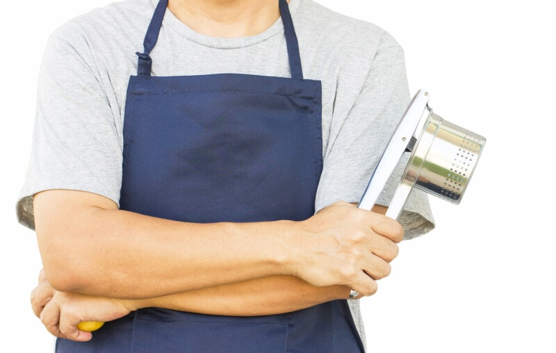Male chef in blue apron holding a potato ricer