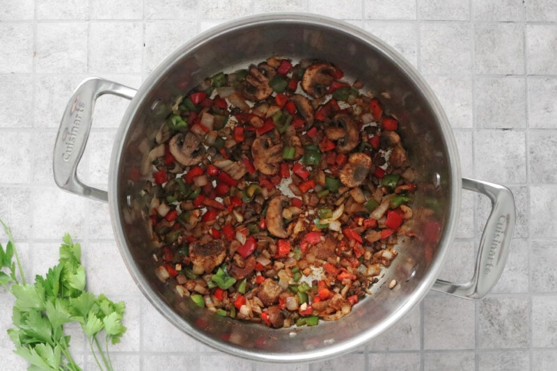 browned peppers, onions, and mushrooms in a large pot