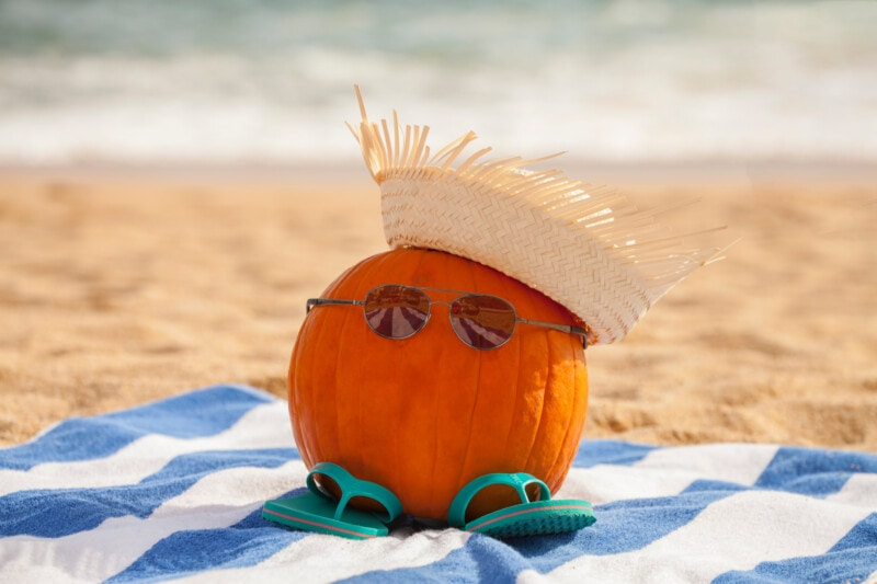 A pumpkin on a towel on a beach wearing sunglasses and a straw hat